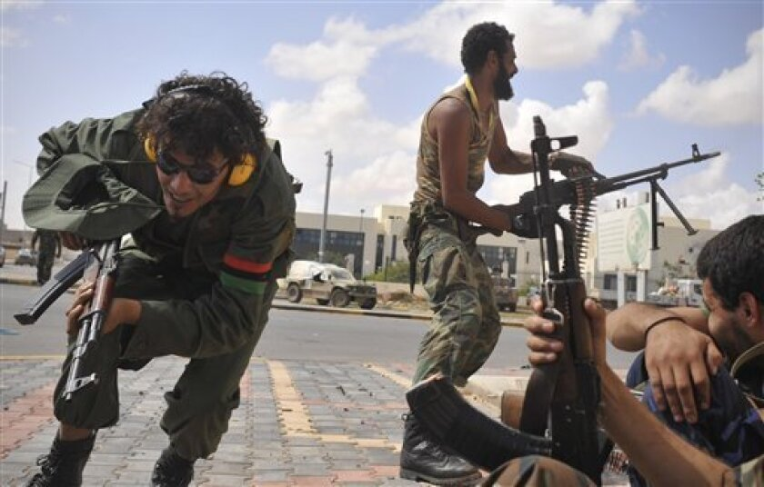 Libyan revolutionary fighters attack pro-Gadhafi forces beside the Ouagadougou conference center of Sirte, Libya, Sunday, Oct. 9, 2011. Rebel forces have besieged Sirte since mid September and are still facing fierce resistance from loyalists inside the home town of Libya's ousted leader Moammar Gadhafi. (AP Photo/Bela Szandelszky)