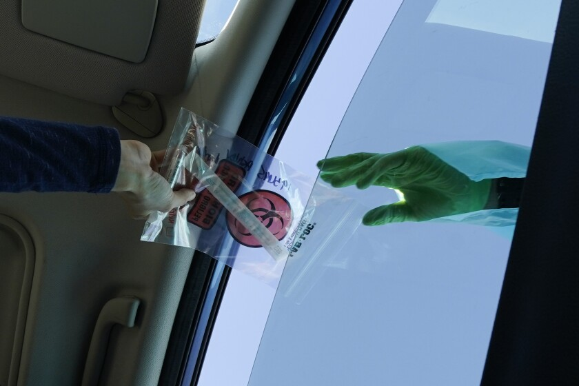 A COVID-19 test is handed through the vehicle window at a mobile testing site on Tuesday, Dec. 1, 2020, in Long Beach, Calif. (AP Photo/Ashley Landis)