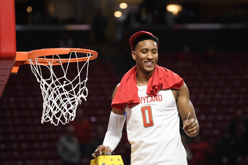 Maryland forward Joshua Tomaic holds a piece of the net after Terrapins won a share of the Big Ten regular season title by defeating Michigan on March 8 in College Park, Md.