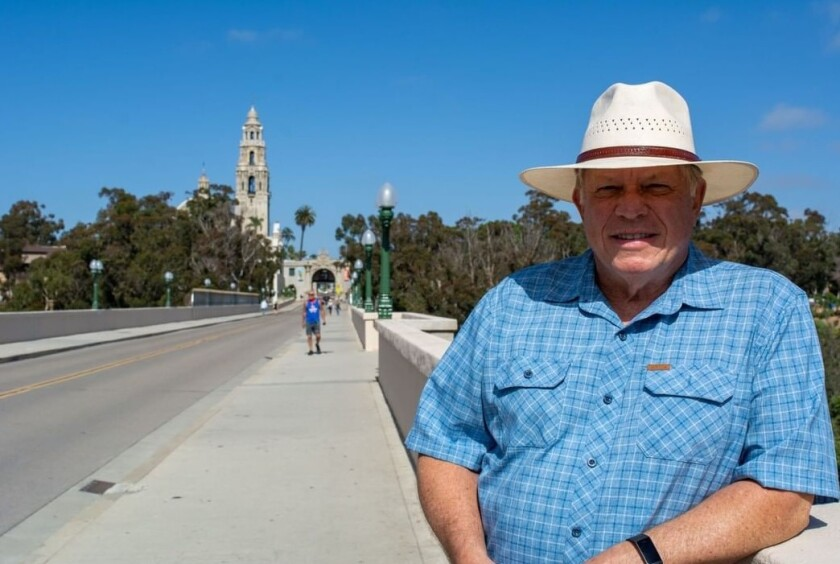 Jim Hughes, long an active Balboa Park volunteer, stands on Cabrillo Bridge leading into the park.