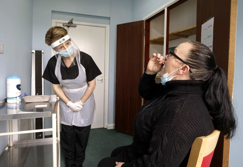 Sarah Hatchett, left, head of care at King Charles Court nursing home oversees the demonstration of a rapid COVID-19 test