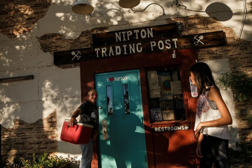 Carl Cavaness and Kiera Freeman joke around outside the trading post in Nipton, Calif.