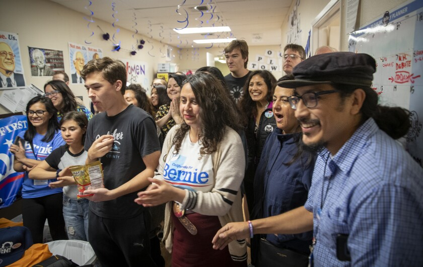 Joesé Hernandez, right, and activist Alicia Rojas, center, join Bernie Sanders campaign volunteers to celebrate Sanders' projected victory March 3 in California.