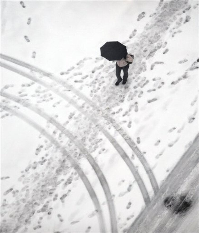 A pedestrian walks down Spring Street in Atlanta Tuesday, Jan. 11, 2011. Atlanta, which has gotten 4 to 7 inches in a snow storm that battered the South, has just eight snow plows. (AP Photo/Mike Stewart)