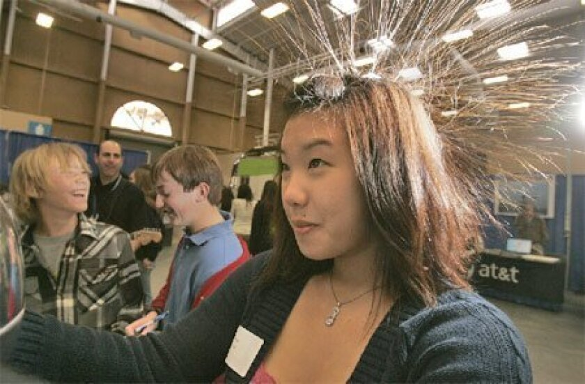 At the 11th San Diego County High Tech Fair yesterday, Denise Ngo, 17, a Westview High School student, tried out the Van De Graaff generator, which caused her hair to fly. More than 2,000 students attended the fair at the Del Mar Fairgrounds. (John Gastaldo / Union-Tribune)