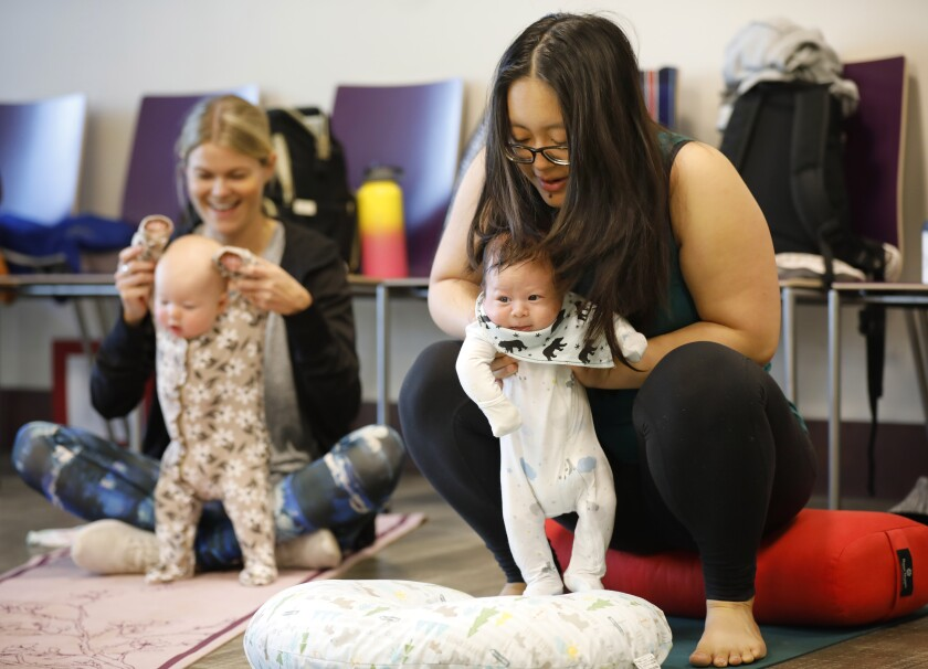 Mary VanBuhler and her 6-month-old son, Avery, enjoy Storytime Yoga in the community room at the Mission Hills-Hillcrest Harley & Bessie Knox Library. At left is Hannah Speicher and her daughter Ruby. The library's community room hosts lunchtime lectures for seniors, a mobile makers lab for teens and many other free public events.