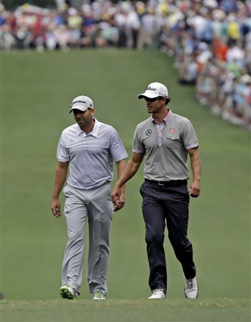Sergio Garcia, left, of Spain, walks with Adam Scott, of Australia, up the first fairway during the second round of the Masters golf tournament Friday, April 12, 2013, in Augusta, Ga. (AP Photo/David J. Phillip)