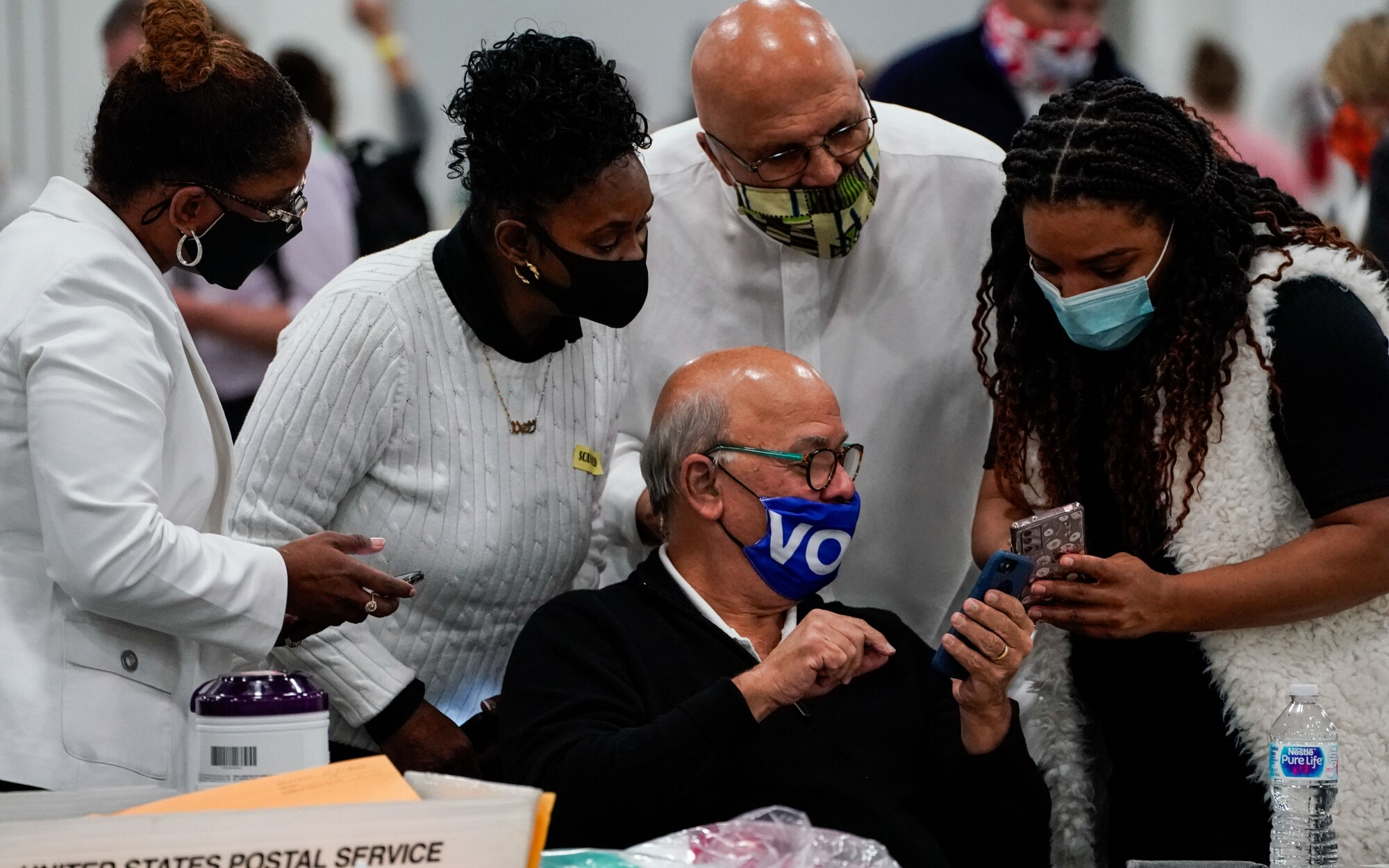 Election workers look at their cellphones