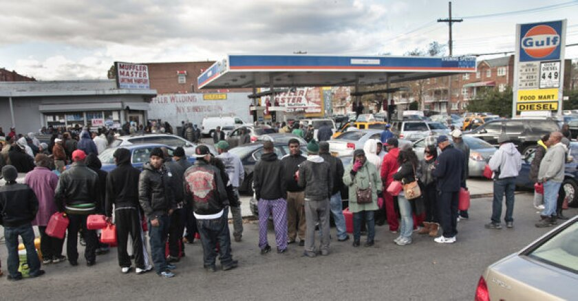 Customers with portable containers wait for gas pumps to open at a service station Saturday in Brooklyn.