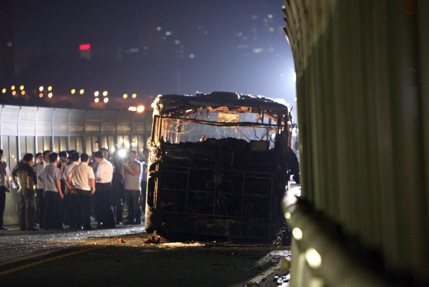 Investigators at the scene of a bus fire Friday in Xiamen, China, that killed 47 people, including the disgruntled man authorities said set the blaze.