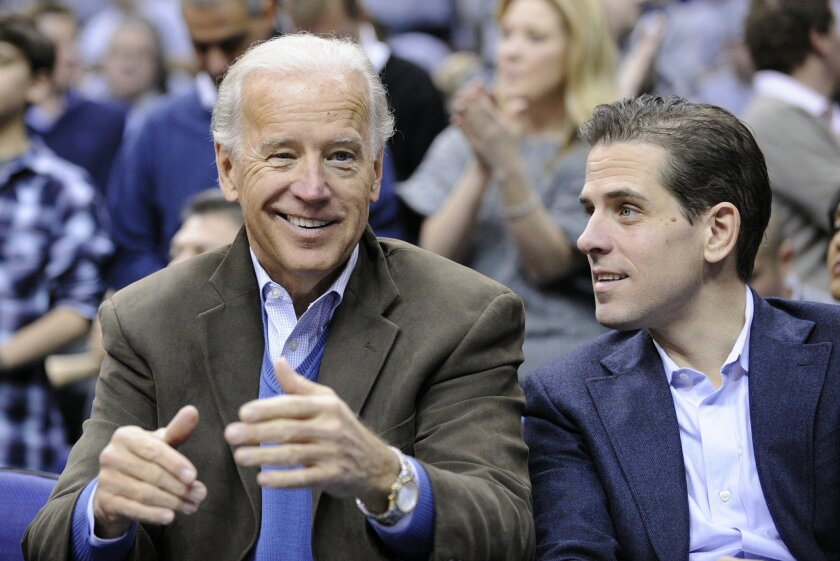FILE - In this Jan. 30, 2010, file photo, Vice President Joe Biden, left, with his son Hunter, right, at the Duke Georgetown NCAA college basketball game in Washington. Hunter Biden is expressing regret for being discharged from the Navy Reserve amid published reports that he tested positive for co