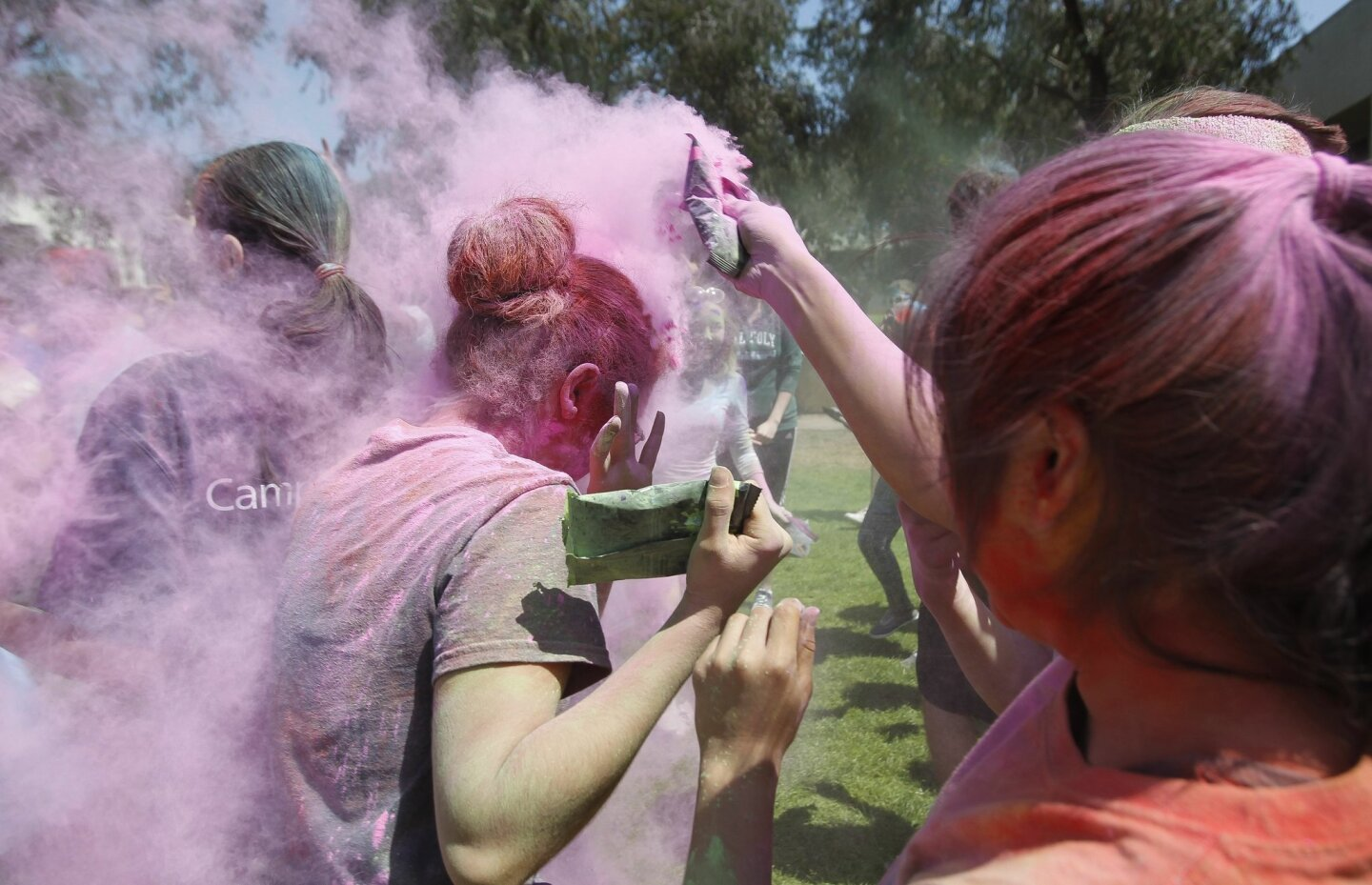 UCSD student Kathleen Bonilla gets covered with colored powder.