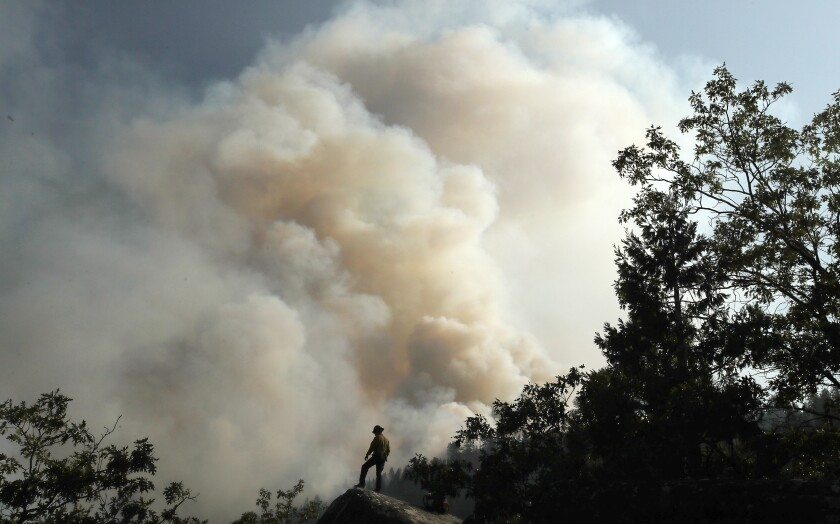 A firefighter is dwarfed by the plume of the Dixie fire