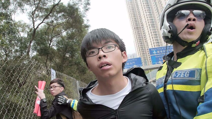 Hong Kong pro-democracy activist Joshua Wong is detained by a police officer after he and others ran onto a road on May 19, 2016.