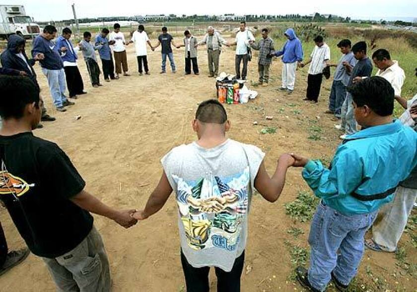Farmworkers join hands in prayer at their camp in Carlsbad, in north San Diego County. Local churches and volunteers provide spiritual support, food and clothing.