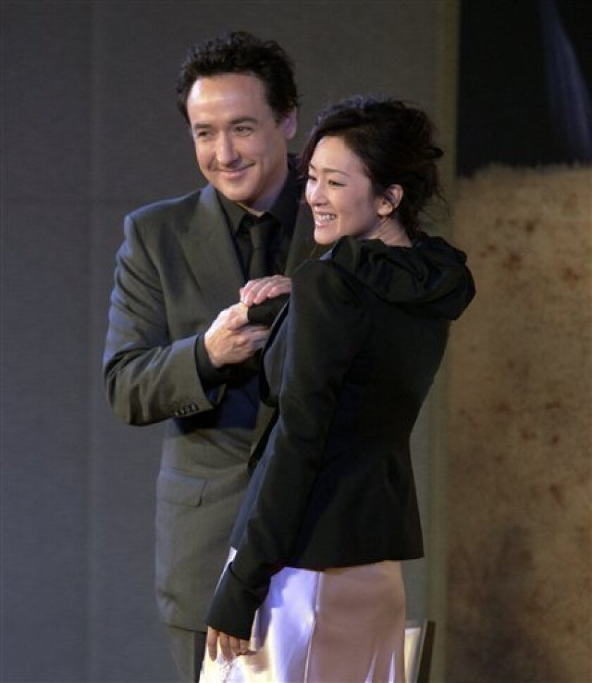 "American actor John Cusack, left and Chinese actress Gong Li pose for photographers during a press conference for their movie ""Shanghai"" in Beijing, China, on Thursday, June 10, 2010. (AP Photo/Ng Han Guan)"