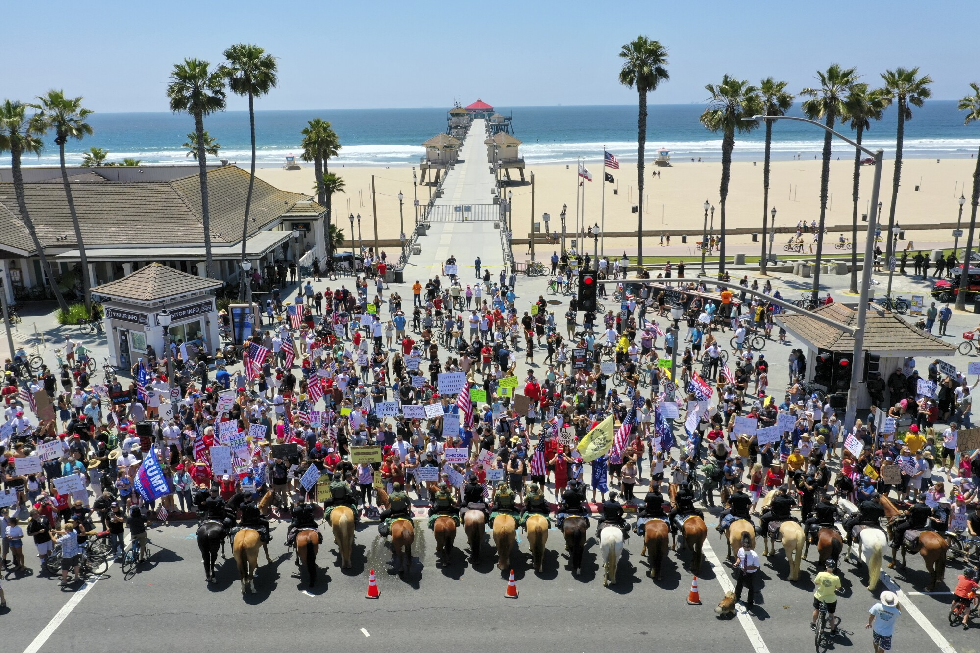 Protesters rally at the foot of the Huntington Beach Pier against COVID-related restrictions on May 1.