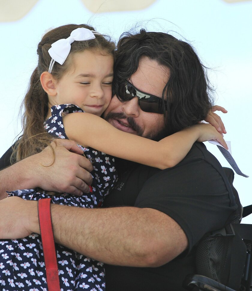 Jason Ross a USMC staff sergeant, who lost both his legs in 2011, gets a big hug from his daughter Jackie, just prior to the Gary Sinise Foundation donating a home to them.