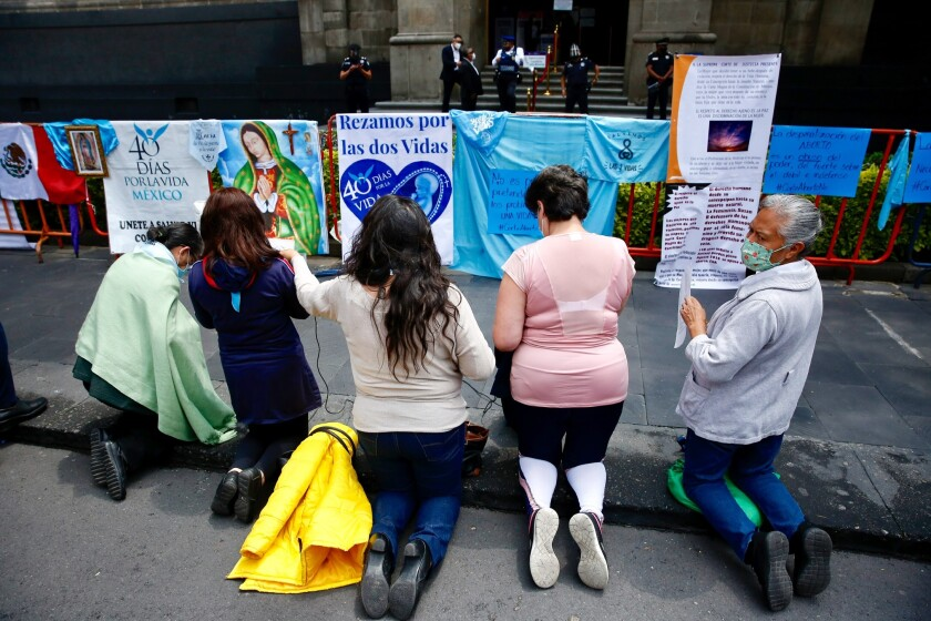 """A group of anti-abortion women pray in front of """"pro-life"""" and religious protest signs"""