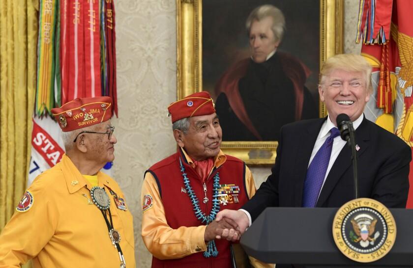 El presidente Donald Trump (d) se reúne con codificadores navajos Peter MacDonald (c) y Thmas Begay, en la Oficina Oval en Washington.