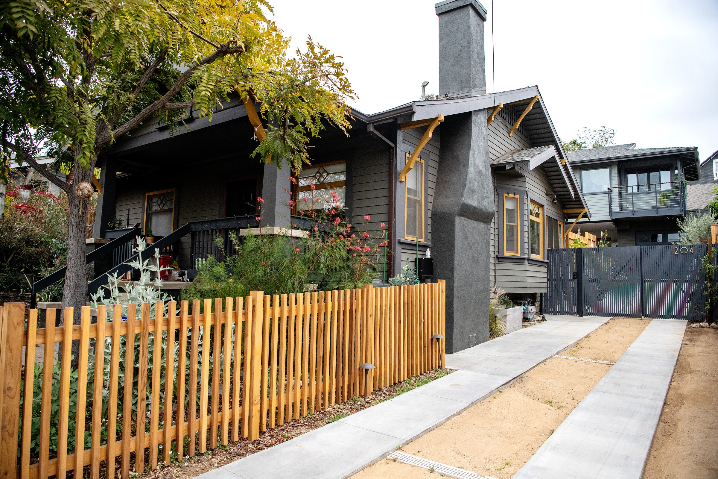 A gray house with yellow trim has a wood picket fence in the front yard and an accessory dwelling unit elevated behind it.