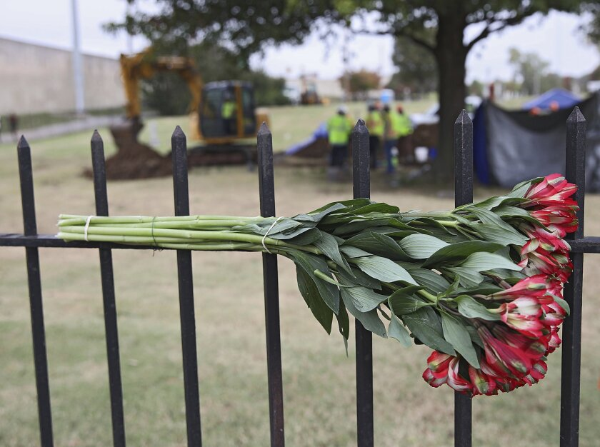 Flowers left by a mourner hang on a fence at Oaklawn Cemetery