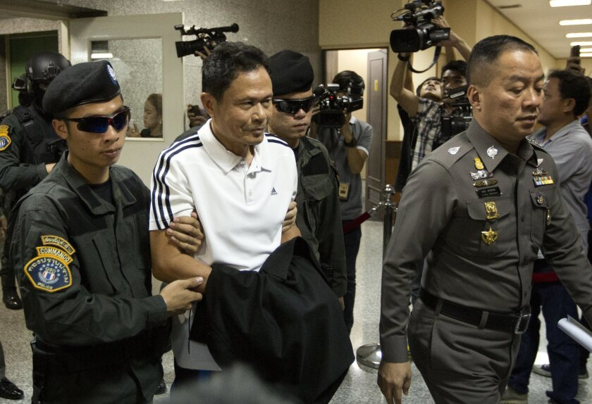 Suspect Prathin Janket is escorted past waiting media at police headquarters in central Bangkok, Thailand, Thursday, Nov. 26, 2015. Thai police say they have uncovered a plot by political opponents of the military government to stage an armed attack that would cause chaos during upcoming events commemorating the country's monarchy. (AP Photo/Mark Baker)