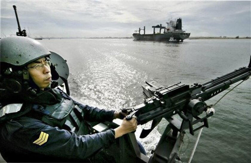FILE - This May 27, 2004 file photo shows a Singaporean sailor manning a machine gun during a patrol of the waters off Singapore. Singapore's Navy is warning that a terrorist group is planning attacks on oil tankers in the Malacca Straits. According to an advisory issued Wednesday, March 3, 2010, by the Navy's Information Fusion Center seen by The Associated Press, terrorists may also be targeting other vessels in the shipping lane off Malaysia's east coast. (AP Photo/Ed Wray, File)