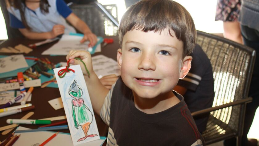 Alexander Allbort shows off his bookmark, featuring one his favorite Dr. Seuss characters, The Grinch.