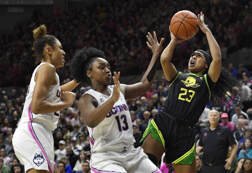 Oregon's Minyon Moore, right, shoots as Connecticut's Olivia Nelson-Ododa, left, and Christyn Williams, center, defend in the second half of an NCAA college basketball game, Monday, Feb. 3, 2020, in Storrs, Conn. (AP Photo/Jessica Hill)