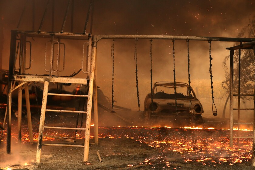 A burned car and swing set are surrounded by embers from the Kincade fire on Thursday in Geyserville, Calif.