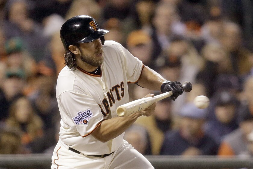 FILE - In this Wednesday, April 22, 2015 file photo, San Francisco Giants' Madison Bumgarner bunts on a pitch from Los Angeles Dodgers' Clayton Kershaw in the third inning of a baseball game in San Francisco. Bumgarner was out on a sacrifice bunt in the at-bat. Under new rules for this abbreviated baseball season delayed by the coronavirus, all games will include the designated hitter -- so National League pitchers will no longer have a chance to hit. (AP Photo/Ben Margot, File)