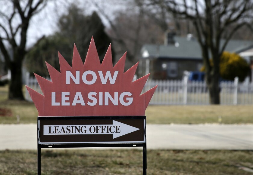 """A """"now leasing"""" sign with a red starburst on top of a white arrow that says """"leasing office"""""""