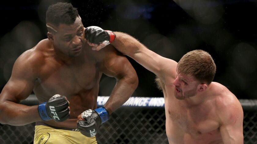 Stipe Miocic lands a right hand against Francis Ngannou during a heavyweight championship mixed martial arts bout at UFC 220.