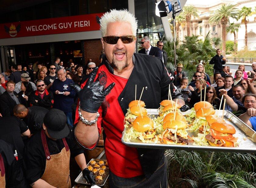 Guy Fieri poses at Guy Fieri's Vegas Kitchen & Bar at The Quad Resort & Casino on April 4, 2014 in Las Vegas, Nevada