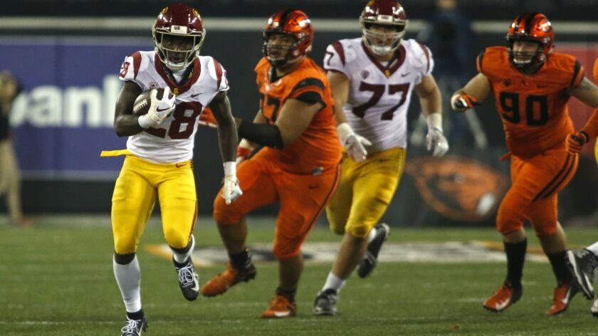 Southern California's Aca'Cedric Ware (28) breaks through the line and heads up field against Oregon