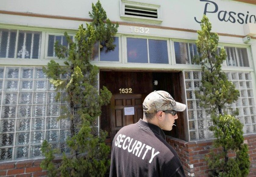 A security guard who declined to give his name stands outside House of Kush in 2010.
