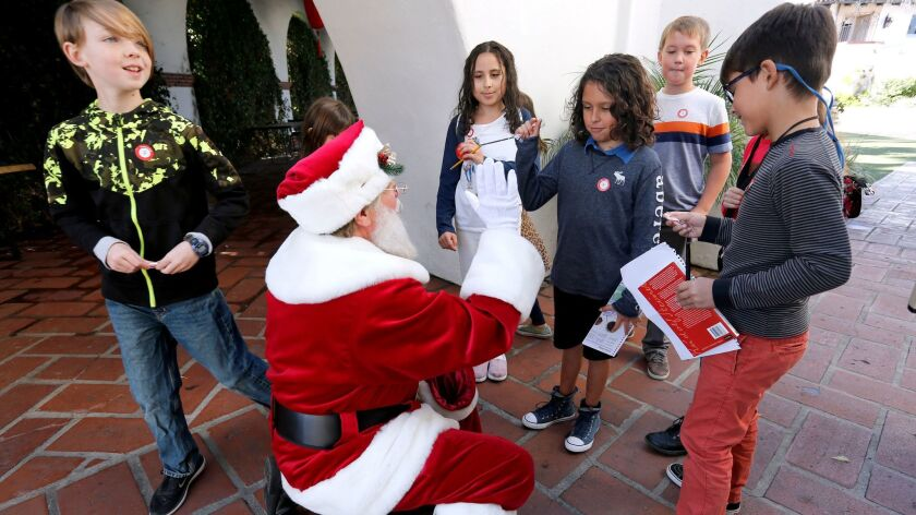 Bowers Museum carpenter Jeff Cassidy, who also performs in the role of Santa Claus, greets Linden Tr