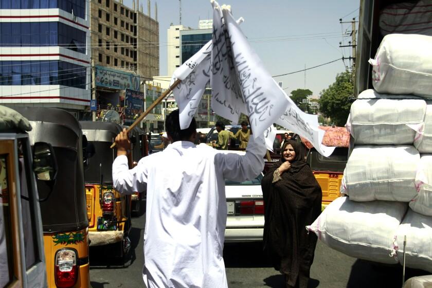 A boy sells Taliban flags in  the street