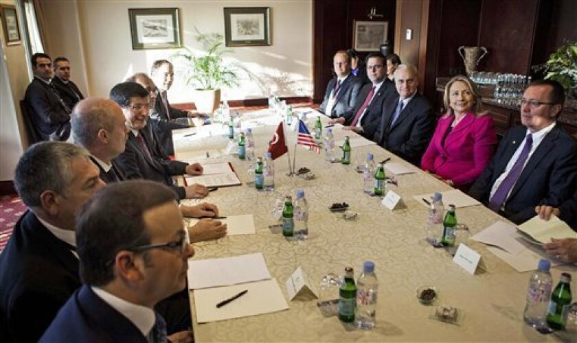 """U.S. Secretary of State Hillary Rodham Clinton, second right, meets with Turkish Foreign Minister Ahmet Davutoglu, fourth from front on left side, during a bilateral meeting at a hotel Saturday, March 31, 2012 in Istanbul, Turkey. Clinton is in Turkey to attend the second meeting of the """"Friends of the Syrian People."""" (AP Photo/Brendan Smialowski, Pool)"""