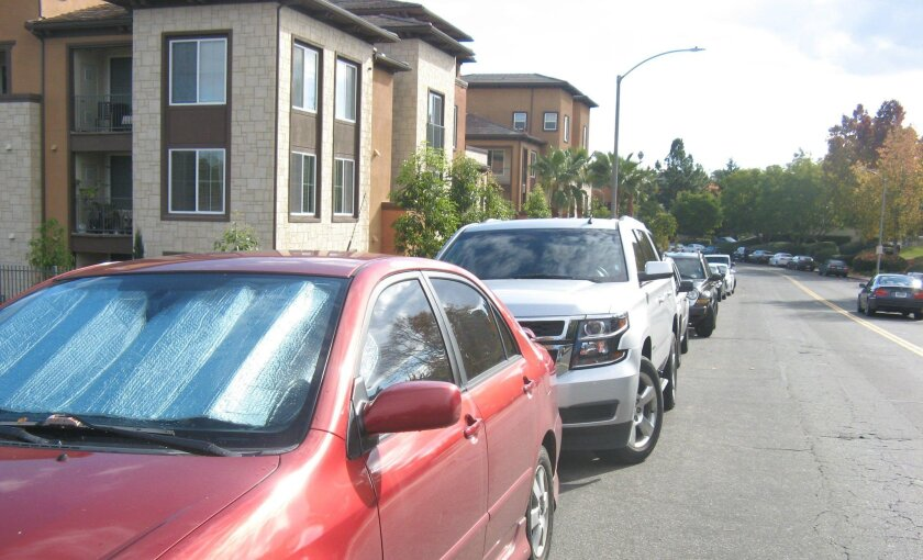 Cars crowd along the curbs of Breeze Hill Road in this December 2015 photo. Parking is often at a premium on the street, which is lined with apartments and condos. Residents are fighting plans to build another apartment complex.
