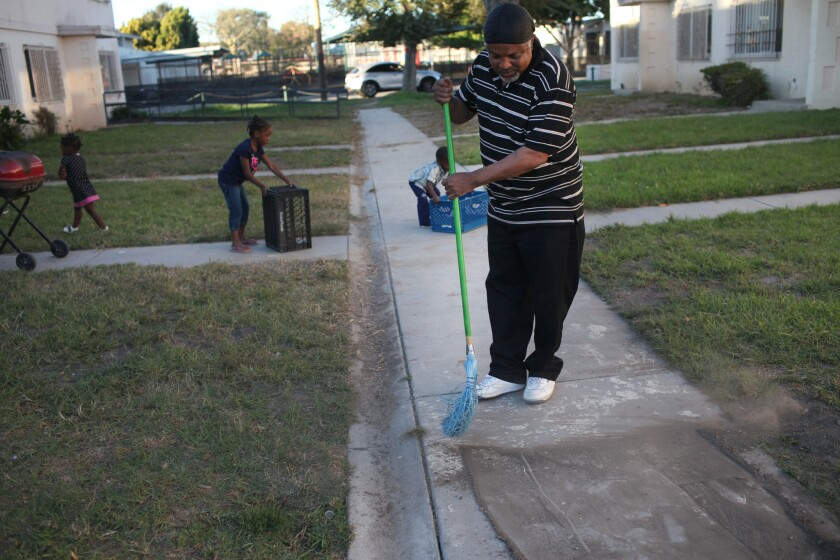 Craig McGruder sweeps the sidewalk leading to his sons' home in the Jordan Downs housing complex in Watts.