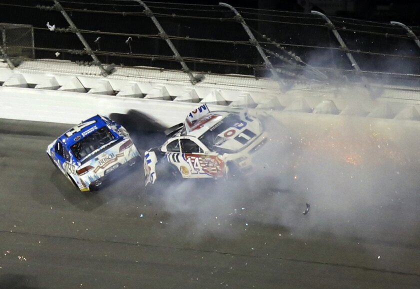 Kevin Harvick, left, wrecks with Brian Vickers (14) coming out of turn 1 during the Sprint Unlimited auto race at Daytona International Speedway, Saturday, Feb. 13, 2016, in Daytona Beach, Fla. (AP Photo/David Graham)