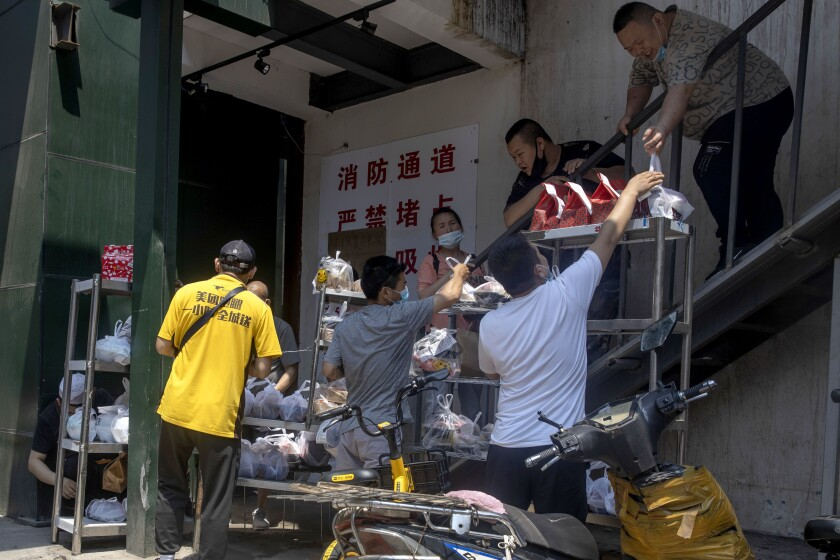 Deliverymen collect food orders in Beijing on Friday, June 19, 2020. China declared a fresh outbreak in Beijing under control after numbers for new cases stabilized as hundreds of thousands are tested. (AP Photo/Ng Han Guan)