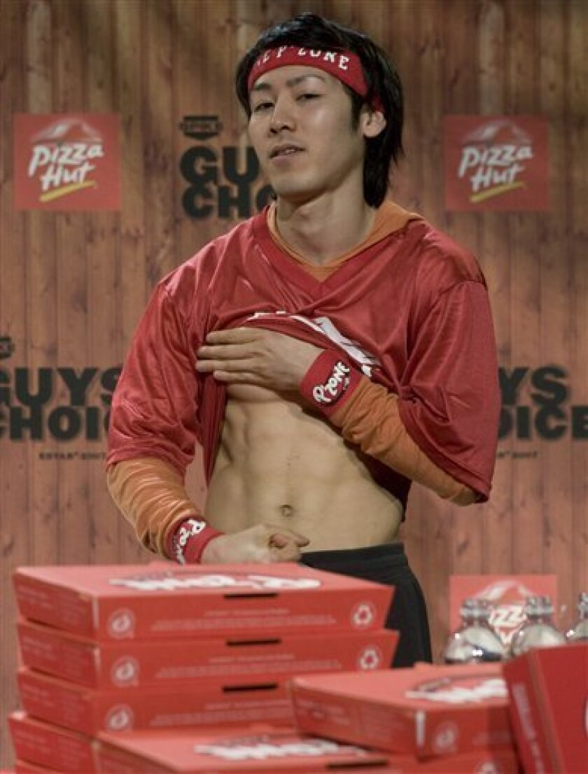 Takeru Kobayashi from Japan, shows his abdominals after defeating his opponent Joey Chestnut in a pizza-eating competition in Los Angeles on Saturday, May 30, 2009. (AP Photo/Hector Mata)