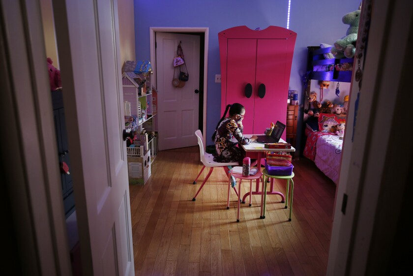 A nine-year-old girl attends online class in her bedroom