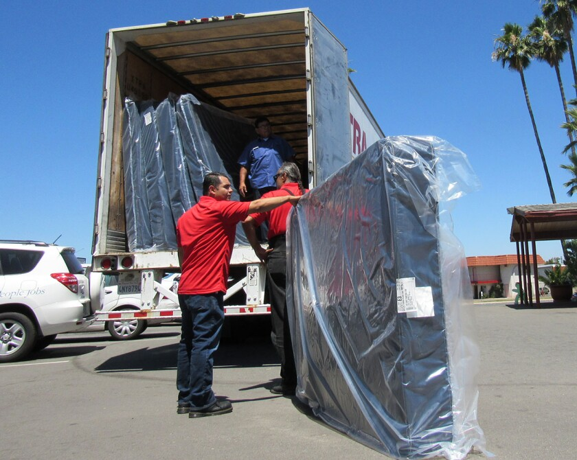 Employees of Jerome's Furniture deliver 60 mattresses to the East County Transitional Living Center in 2017.