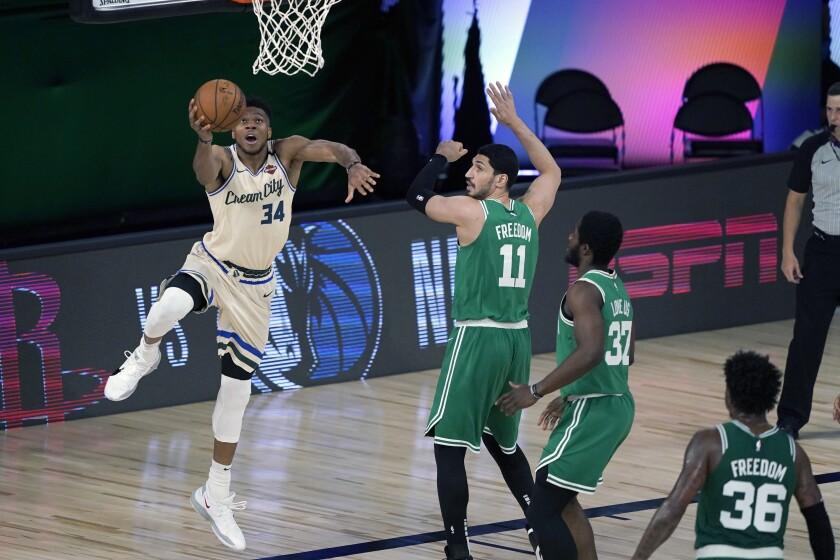 Giannis Antetokounmpo, de los Bucks de Milwaukee, salta hacia la cesta frente a Enes Kanter, Semi Ojeleye y Marcus Smart (36), de los Celtics de Boston, en el duelo del viernes 31 de julio de 2020 (AP Foto/Ashley Landis, Pool)
