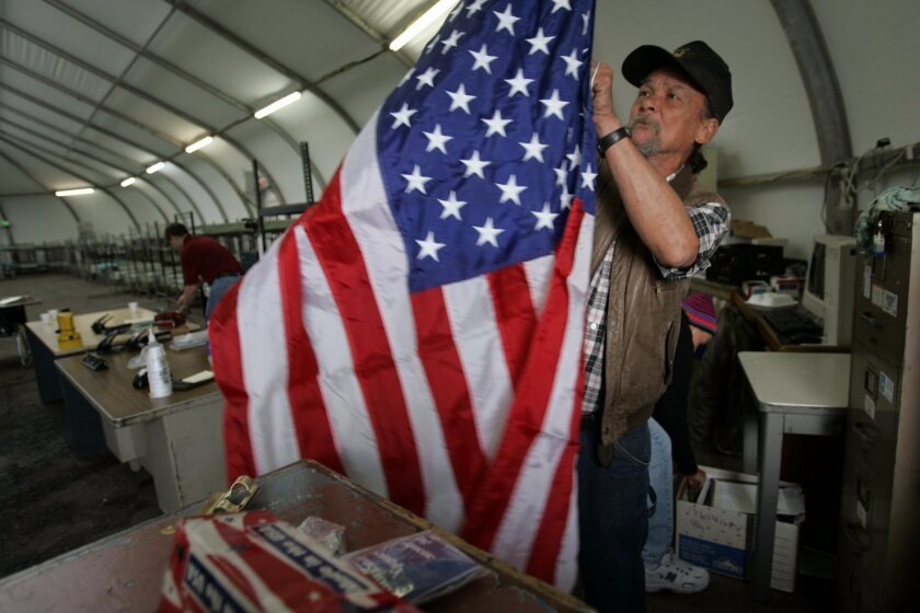 In a Dec. 5, 2007 file photo, John Chesney put together a flag for a winter shelter for homeless veterans, run by the Veterans Village of San Diego.