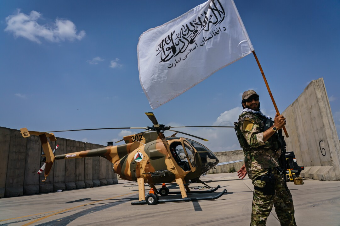 A Taliban fighter with white Taliban flag in front of a camouflage helicopter